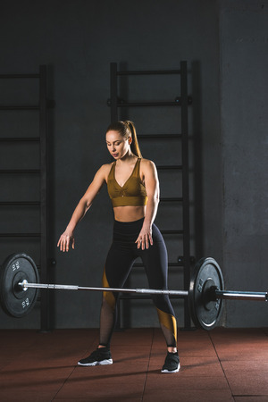 Young caucasian sportswoman letting go barbell  in sports hall Stockfoto
