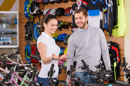 smiling young manager showing bicycles to customer in bike shop Stock fotó