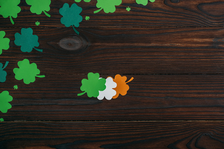 top view of clovers in colors of irish flag on wooden table