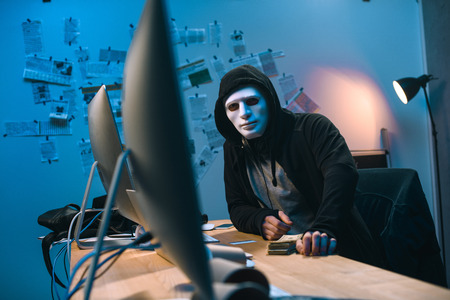 hooded hacker in mask with stack of money on desk Stock Photo