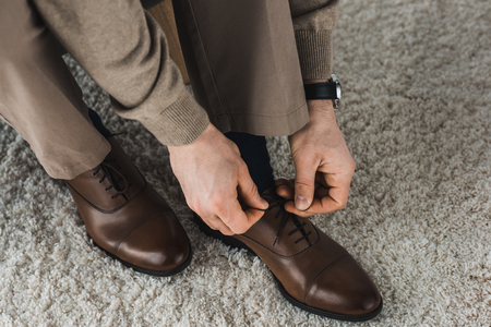 Close-up view of man tying shoelaces of his leather shoes