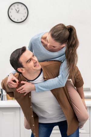 beautiful wife piggybacking on husband at home