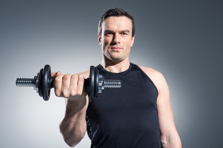Young man athlete exercising with dumbbell on grey background 스톡 콘텐츠