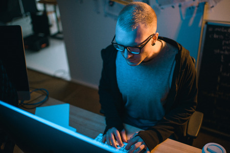 high angle view of hacker developing malware in dark room Stock Photo