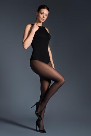 Seductive woman in black tights and bodysuit on dark background Фото со стока