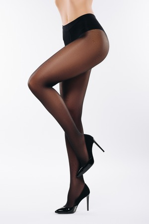 Female legs in black pantyhose isolated on white