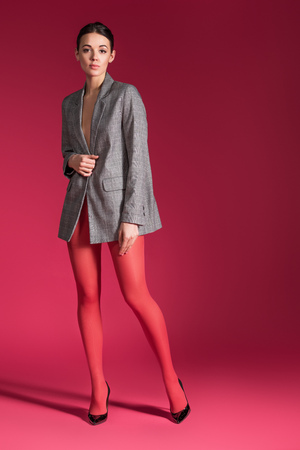 Sensual woman in red nylon tights wearing grey jacket on red background
