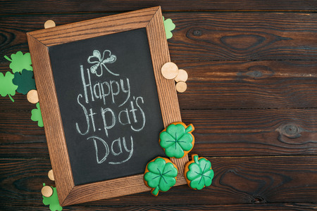 close-up view of wooden frame with happy st patricks day inscription and golden coins on table Stok Fotoğraf