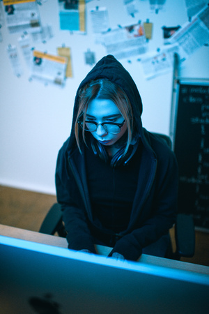 high angle view of young female hacker developing malware under blue light Banco de Imagens