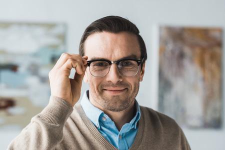Smiling adult man fixing his eyeglasses