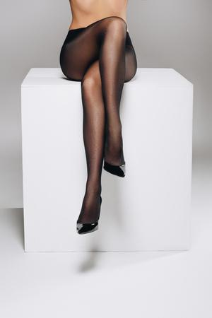 Woman wearing black pantyhose posing on white box with legs crossed