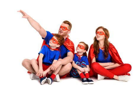super family in costumes sitting together and looking away isolated on white