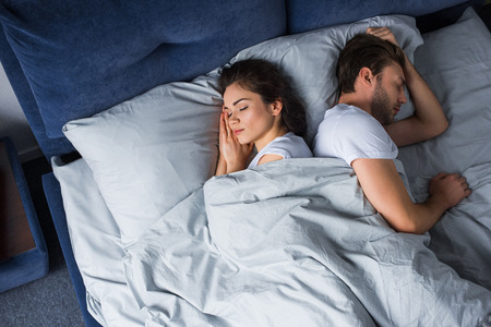 Young couple sleeping in bed in modern bedroom