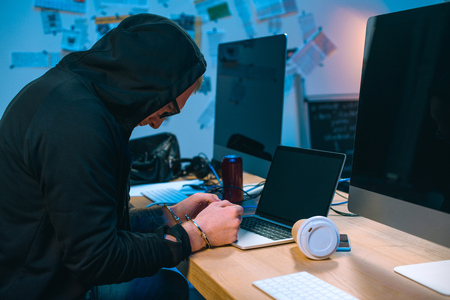 handcuffed hacker in hoodie in front of laptop at workplace Stock Photo