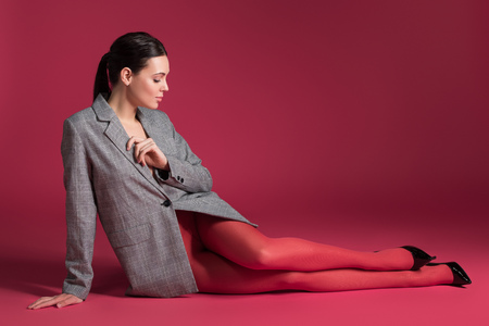 Slim woman in red pantyhose and grey jacket lying on red background 免版税图像
