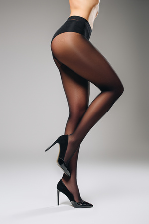 Female legs in black pantyhose on grey background