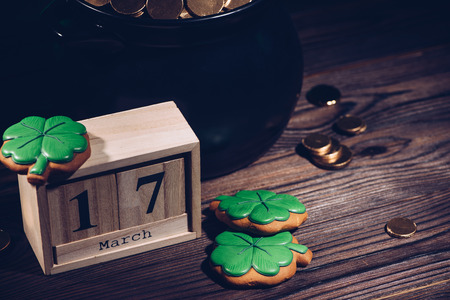 close-up view of calendar, cookies in shape of shamrock and pot with golden coins on wooden table Stok Fotoğraf - 112309183