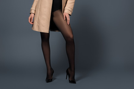 Cropped view of woman wearing black tights and beige trench on dark background Stock Photo