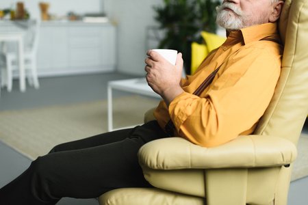 cropped shot of bearded senior man holding cup and sitting on armchair at home