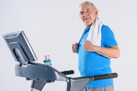 side view of smiling senior man with towel exercising on treadmill isolated on grey Stockfoto