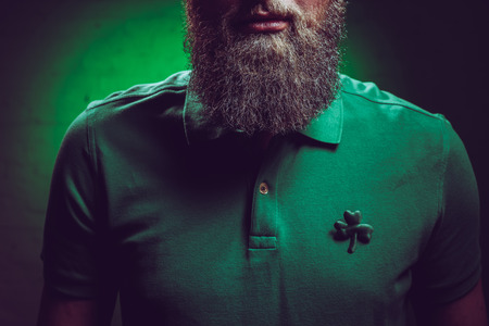 cropped shot of bearded man wearing green polo shirt with shamrock symbol