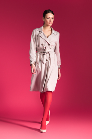 Woman walking in beige trench and heel shoes on red background
