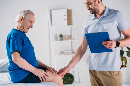 side view of rehabilitation therapist with notepad checking senior mans knee on massage table Archivio Fotografico - 112309285