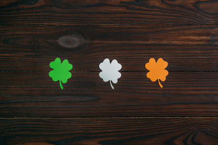 top view of three clovers in colors of irish flag on wooden table