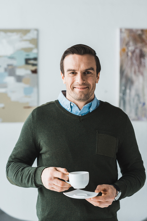 Smiling man holding coffee cup in his hands Stock Photo