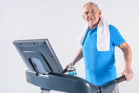 side view of senior man with towel exercising on treadmill isolated on grey Zdjęcie Seryjne