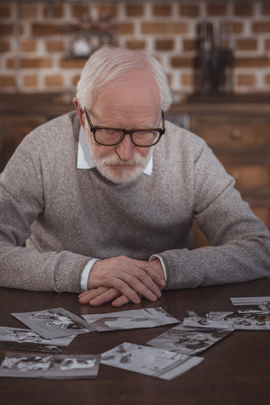 handsome grey hair man sitting at table and looking at photos at home Imagens