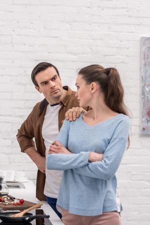 unhappy adult couple having argument at kitchen