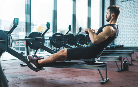 Young sportsman doing exercise on rowing machine in sports center 写真素材 - 112309399