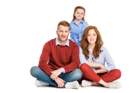 happy redhead family with one child smiling at camera isolated on white