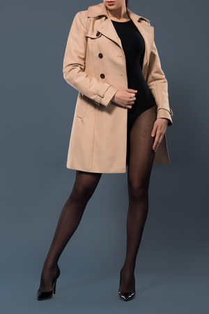 Sensual woman in black nylon tights wearing beige trench on dark background 스톡 콘텐츠