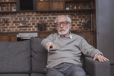 handsome grey hair man changing tv channels with remote control at home