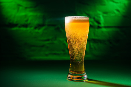 close-up view of glass with fresh cold amber beer in green light, saint patricks day concept