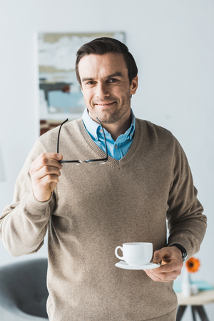 Attractive man holding glasses and cup of coffee Stock Photo