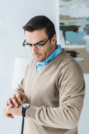 Handsome man in glasses looking at his watch