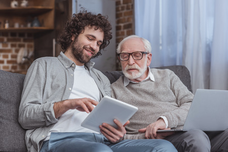 adult son and senior father using tablet and laptop at home