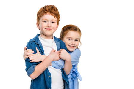 adorable redhead siblings hugging and smiling at camera isolated on white Imagens