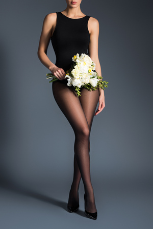 Young woman wearing black bodysuit and tights and holding bouquet of flowers on dark background 免版税图像