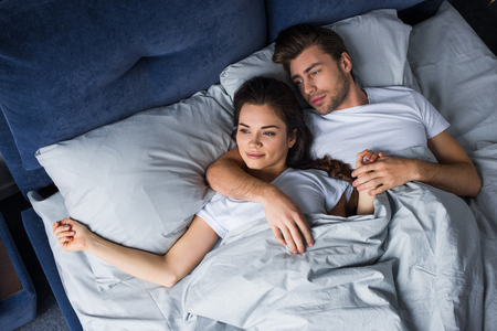 Smiling couple tenderly embracing while lying in bed Stock Photo