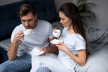 Young couple in loungewear drinking coffee in bed Standard-Bild - 112309840