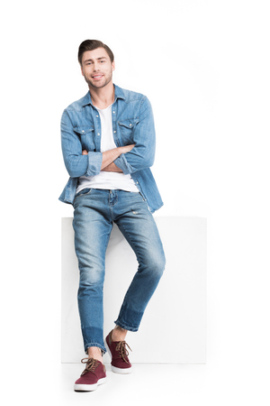 young smiling man in denim leaning on white cube, isolated on white Stock fotó