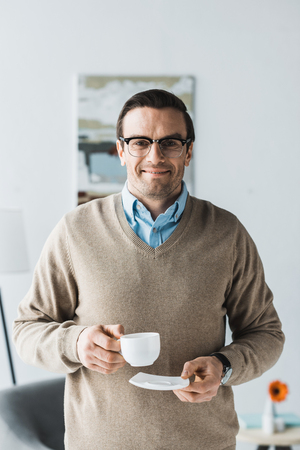 Happy man wearing glasses and holding cup of coffee
