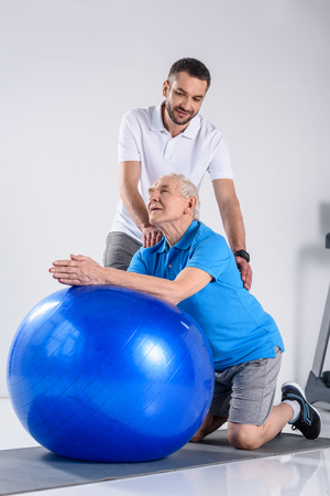 rehabilitation therapist making massage to senior man on fitness ball