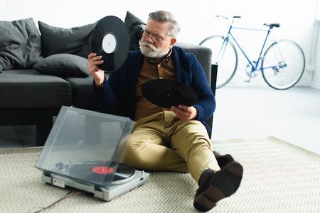 stylish senior man holding vinyl records while sitting on carpet at home