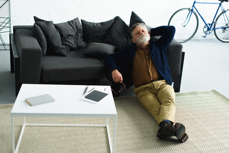 relaxed bearded man sitting on carpet and leaning at sofa at home