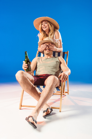 Smiling woman covering face of man holding beer while sitting in deck chair on blue background Stock Photo